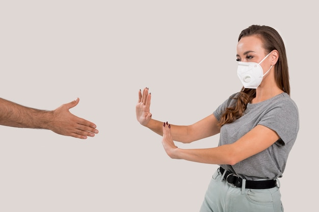 Woman with face mask refusing hand shake