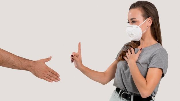 握手を拒否するフェイスマスクを持つ女性