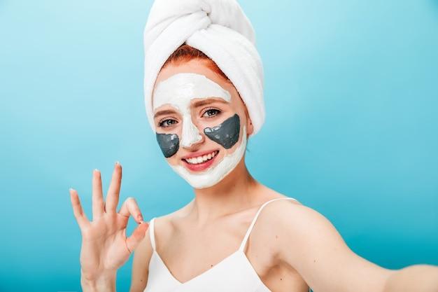 大丈夫な兆候を示して笑っているフェイスマスクを持つ女性。スパトリートメントをしながら自分撮りをしている女性モデル。