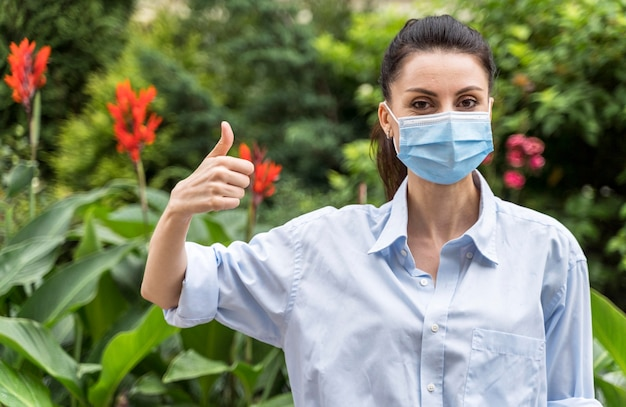 親指を立てるサインを示すフェイスマスクを持つ女性