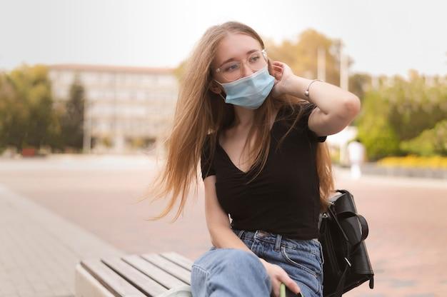 ベンチに座っているフェイスマスクを持つ女性