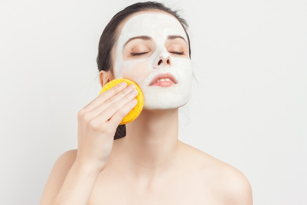 Woman with face mask and sponge