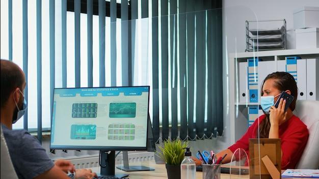 デスクトップを見て統計を分析している電話で話しているフェイスマスクを持つ女性。コンピューターの前でスマートフォンで話すリモートチームとチャットする職場で働くフリーランサー