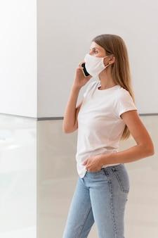 電話で話しているフェイスマスクを持つ女性