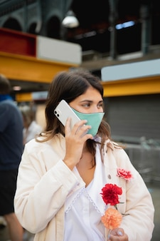 Woman with face mask talking on the phone while holding flowers