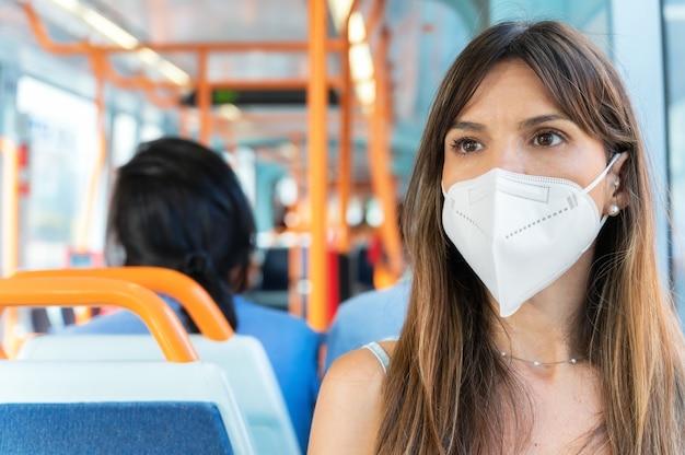 Женщина с маской для лица едет на трамвае во время вспышки коронавируса. фото высокого качества