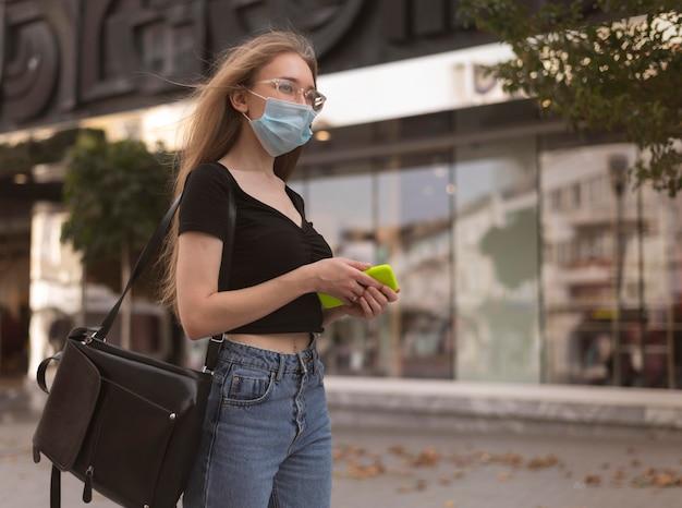 街を歩いているフェイスマスクを持つ女性