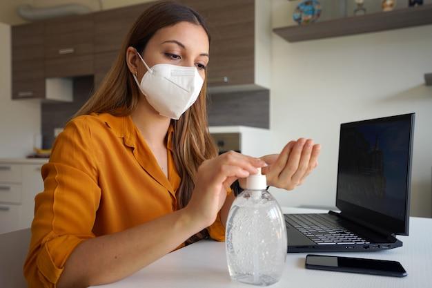 ハンドアルコールジェルを使用してラップトップで自宅で仕事をしているフェイスマスクを持つ女性
