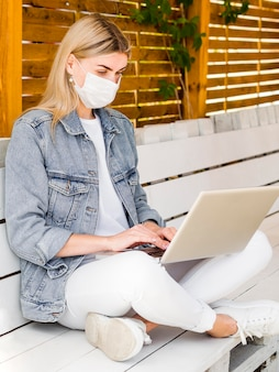 屋外のラップトップに取り組んでフェイスマスクを持つ女性