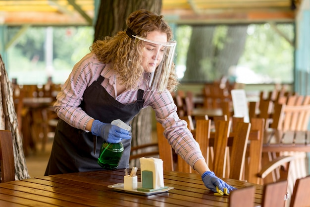 Woman with face protection cleaning tables