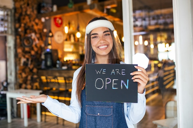 Woman with face shield holding sign we are open