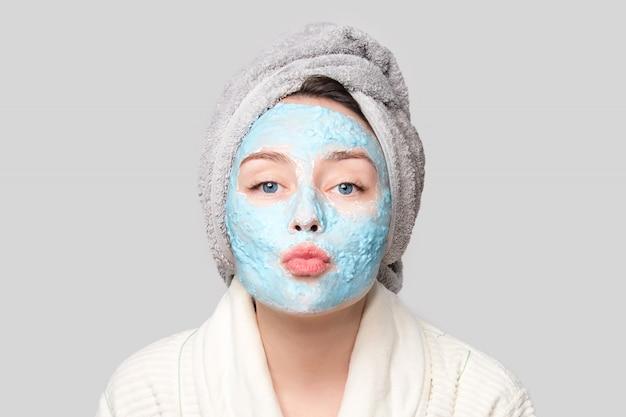 スパサロンまたは自宅、スキンケアテーマで顔の粘土マスクを持つ女性。女の子はアルギン酸化粧品マスクを削除します。フェイスマスク、コピースペース付きのスパ美容トリートメント