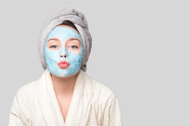 Женщина с лицевой глиняной маской в спа салоне или дома, тема ухода за кожей. девушка снимает альгинатную косметическую маску. маска для лица, спа-салон красоты с копией пространства