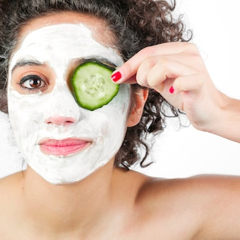 Woman with facial mask applying cucumber slice over one eye