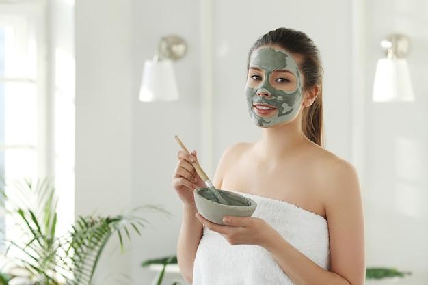 スキンケアのための顔のマスクを持つ女性。美容コンセプト。