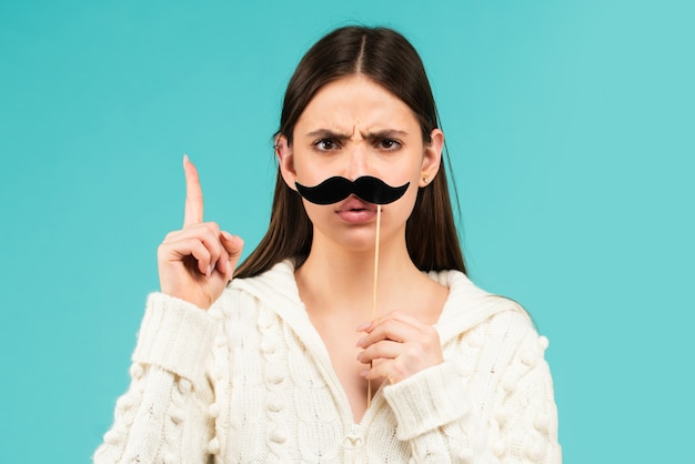 Woman with fake mustache having fun. funny female actress with finger up isolated on blue background.
