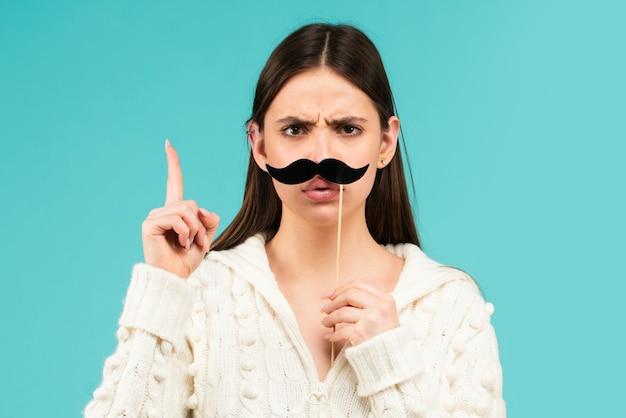 楽しんでいる偽の口ひげを持つ女性。青い背景で隔離の指を上に面白い女性女優。