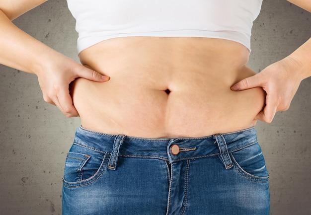 背景に太った腹を持つ女性。