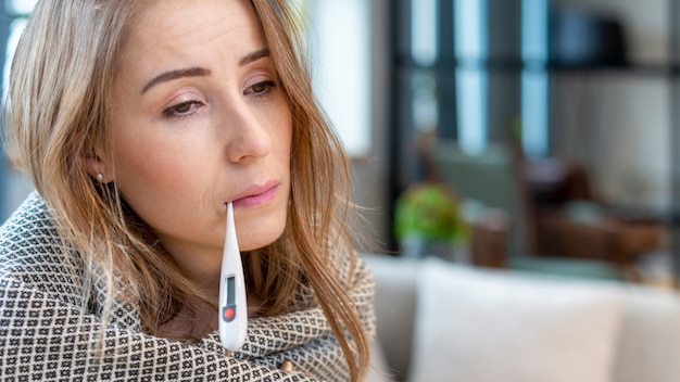 Woman with fever having a thermometer in her mouth