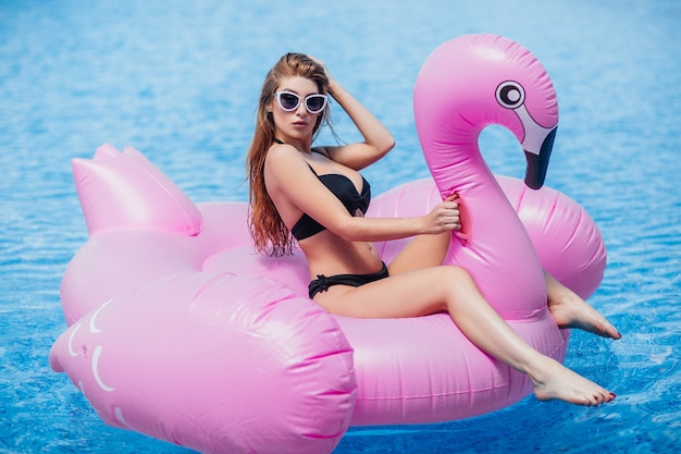 Woman with figure in swimsuit and sunglasses is resting and sunbathing in a pool
