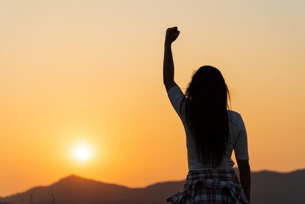 日没時に空気中の拳を持つ女性、やる気、自由