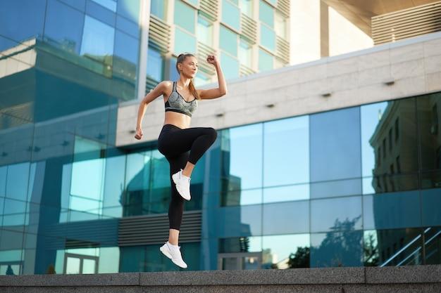 Женщина с подтянутым телом прыгает и бежит на фоне городской городской сцены