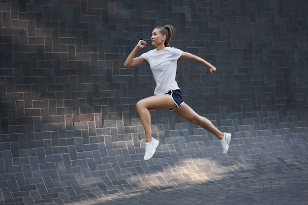 Woman with fit body jumping and running