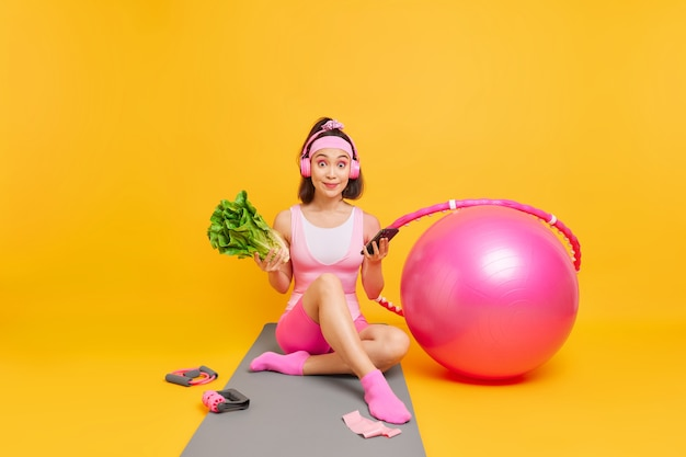 Woman with fit body keeps to healthy diet holds smartphone checks how much calories she burned during training dressed in activewear sits on mat sport equipment