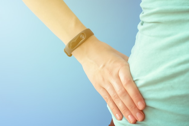 Woman with fitness tracker on hand on blue background