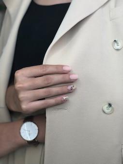 デザインの肌色のマニキュアを持つ女性。爪に新鮮な色の女性のマニキュア