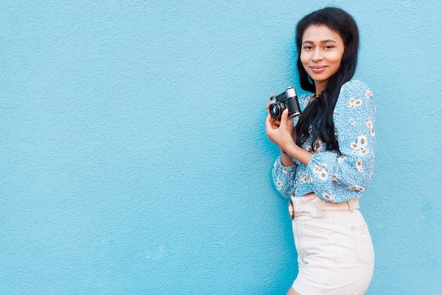 Woman with floral blouse holding a camera