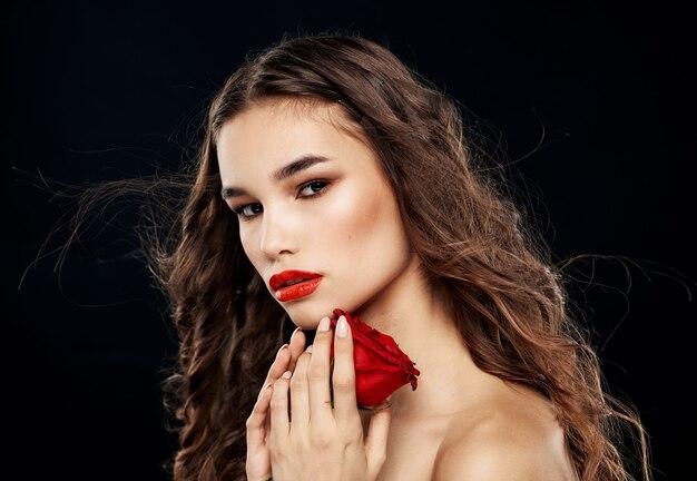 ブルネットモデルの花の暗い背景の肖像画を持つ女性