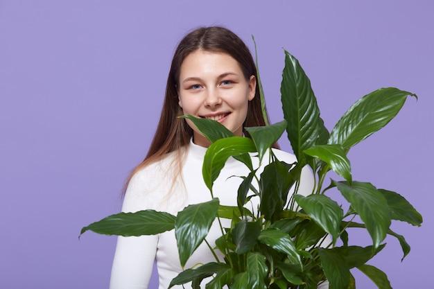 手に緑の花の植物を持つ女性
