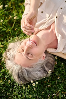 Woman with flower in hand lying on lawn