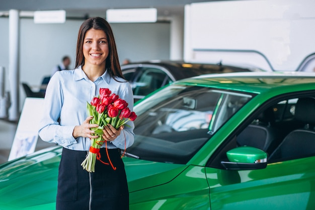 Woman with flowers in a car showroom
