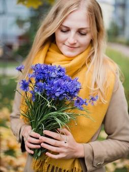 花を持つ女性、女性の手にヤグルマギクの花束
