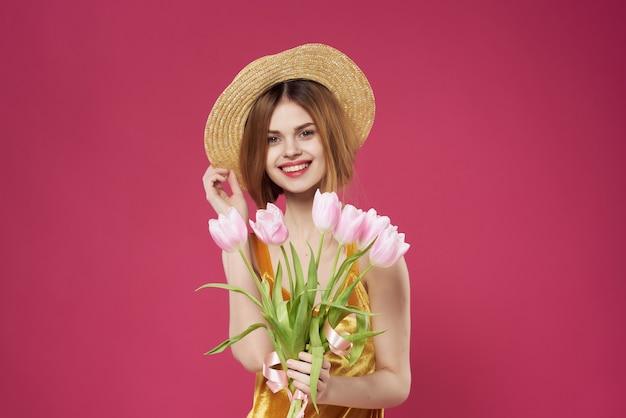花の贈り物女性の休日のファッションピンクの背景を持つ女性