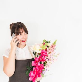Donna con i fiori che parla sul cellulare contro fondo bianco