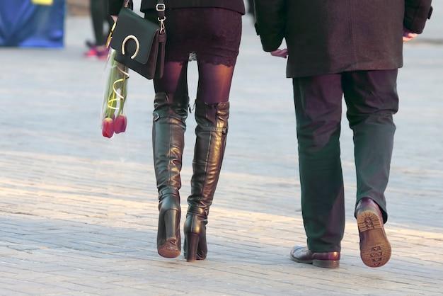 꽃 튤립을 손에 들고 남자 옆을 걷는 여자. 산책하는 사랑하는 커플의 데이트