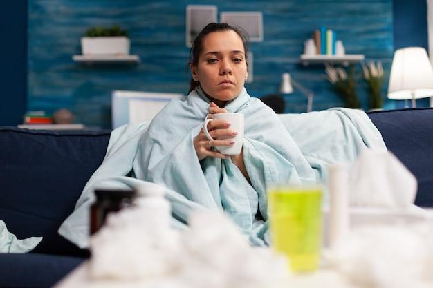 Женщина с гриппом сидит дома, пьет горячий чай, чувствуя себя больным, человек с температурой принимает лекарство ...