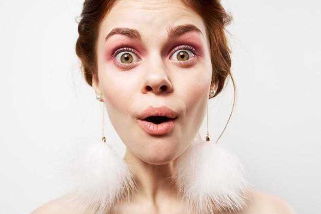 솜 털 귀걸이 밝은 메이크업 감정 클로즈업으로 아름 다운 여자입니다. 고품질 사진