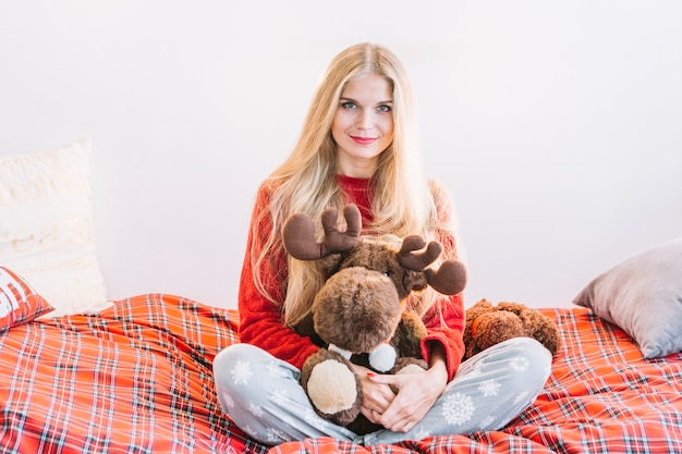 Woman with fluffy toy deer on bed