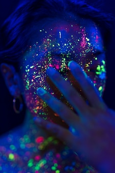 蛍光化粧と顔に手を持つ女性