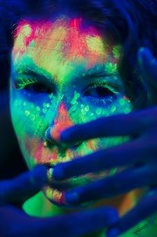 蛍光化粧と彼女の顔に手を持つ女性