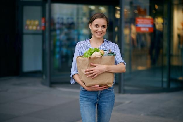 Женщина с едой в картонной сумке на автостоянке супермаркета. счастливый клиент с покупками возле торгового центра, женщина, покупающая фрукты и овощи