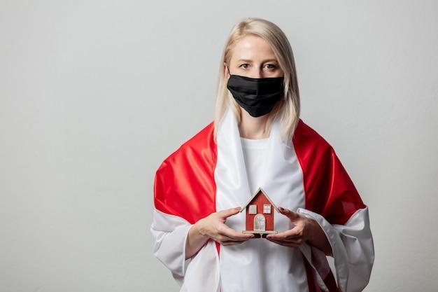 전 벨로루시 국기와 흰 벽에 집 기호를 가진 여자