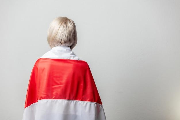 흰 벽에 전 벨로루시 국기를 가진 여자