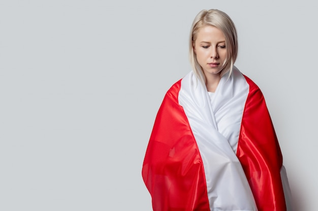 Woman with former national belarus flag on white wall