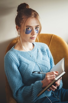 Woman with freckles and ginger hair looking at camera while doing homework and wearing hydrogel eye patches