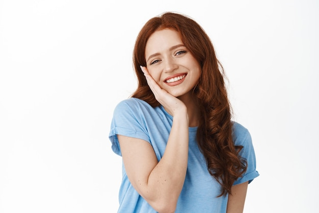 Woman with fresh and clean natural skin, red hair, touching cheek and smiling happy and satisfied, using cleansing facial skincare cosmetic, standing on white